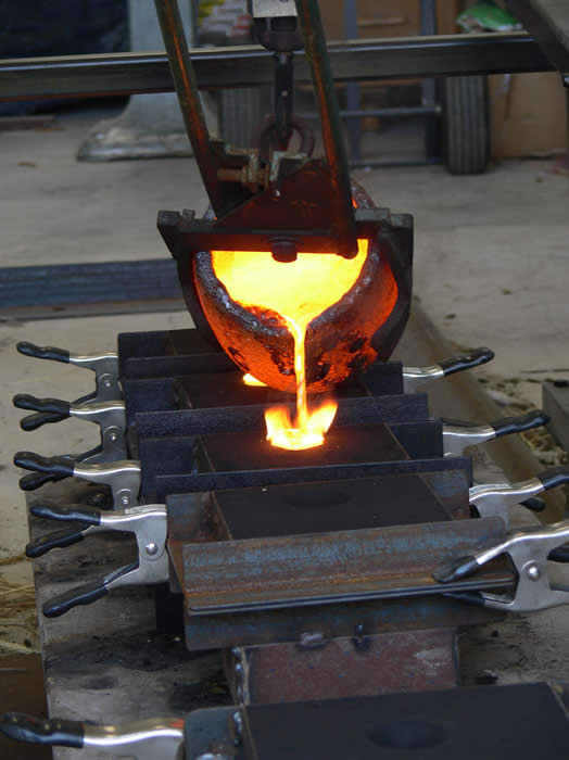 Pouring molten bronze into the sand molds